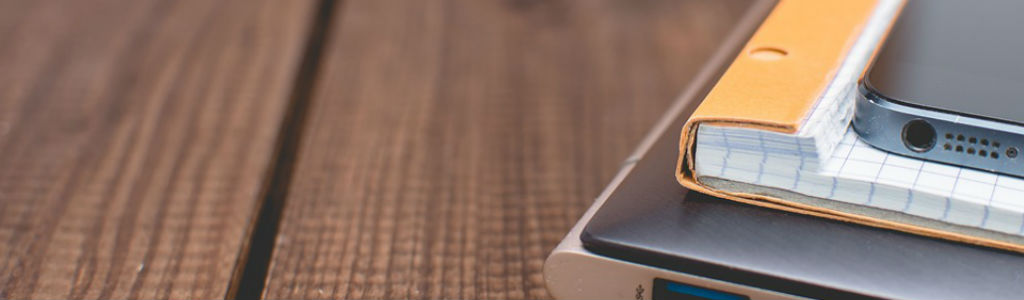 Een laptop, schrijfblok en mobiel op tafel. Neem gerust contact op met OKO.