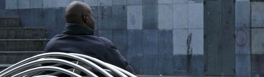 Man op de rug gezien, kijkt voor zich uit op een bankje. Hier vind je meer informatie over OKO.