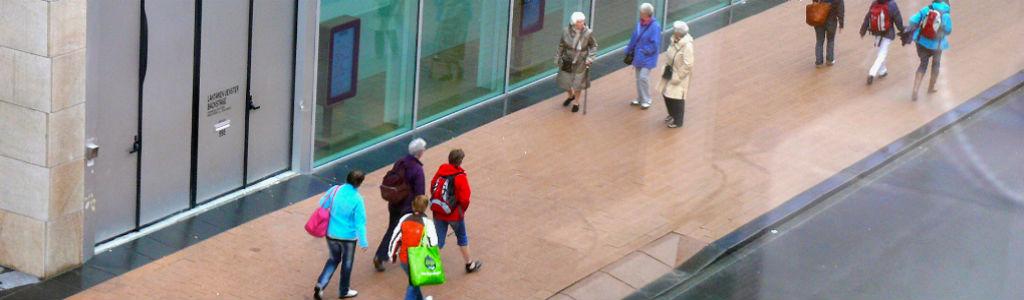 Lopende mensen in een winkelstraat. Overzicht van OKO op het gebied van ontmoeting, bezoekwerk, hulpverlening en zingeving in Rijkerswoerd, Kronenburg en Vredenburg in Arnhem.
